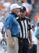 Head coach Joe Philbin of the Miami Dolphins talks to field judge Gary Cavaletto about a call during second quarter action against of the New England...