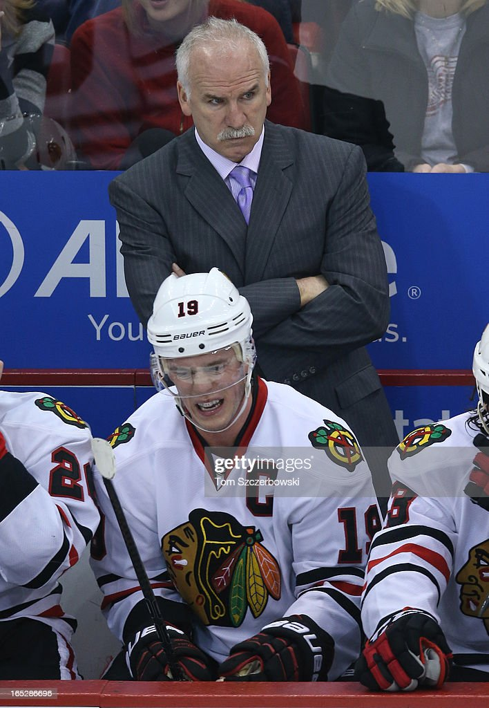 Head coach Joel Quenneville of the Chicago Blackhawks looks on from the bench with Jonathan Toews #19 in front of him during an NHL game against the Detroit Red Wings at Joe Louis Arena on March 31, 2013 in Detroit, Michigan.