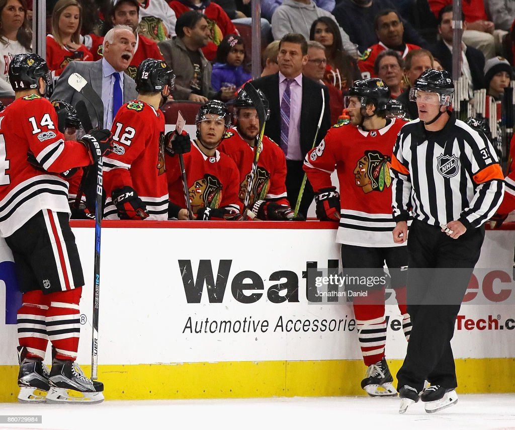 Head coach Joel Quenneville of the Chicago Blackhawks (upper L) yells at referee Kevin Pollock #33 during a game against the Minnesota Wild at the United Center on October 12, 2017 in Chicago, Illinois. The Wild defeated the Blackhawks 5-2.