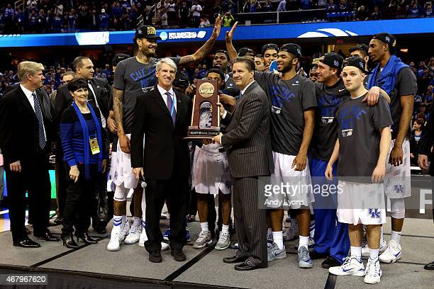 Head coach John Calipari of the Kentucky Wildcats looks on with his team and their trophy after defeating the Notre Dame Fighting Irish during the...