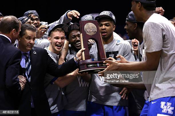 Head coach John Calipari of the Kentucky Wildcats poses with his team and the regional trophy after defeating the Michigan Wolverines 75 to 72 in the...
