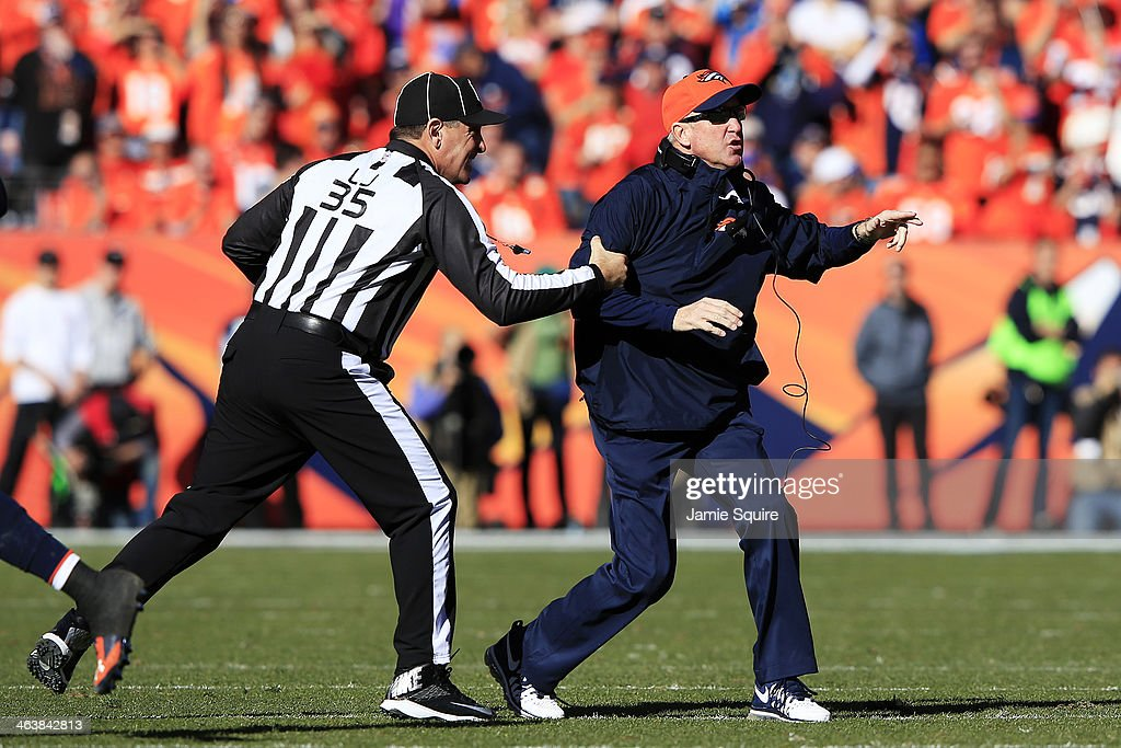 Head coach John Fox of the Denver Broncos gets pulled back by line judge John Hussey during the AFC Championship game against the New England...