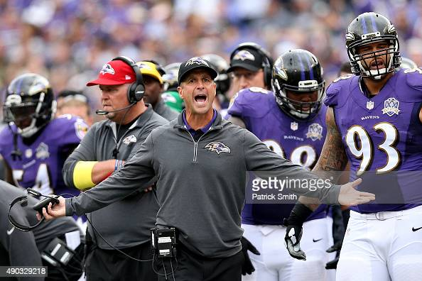 Head coach John Harbaugh of the Baltimore Ravens and defensive end Lawrence Guy of the Baltimore Ravens look on in the third quarter of a game...