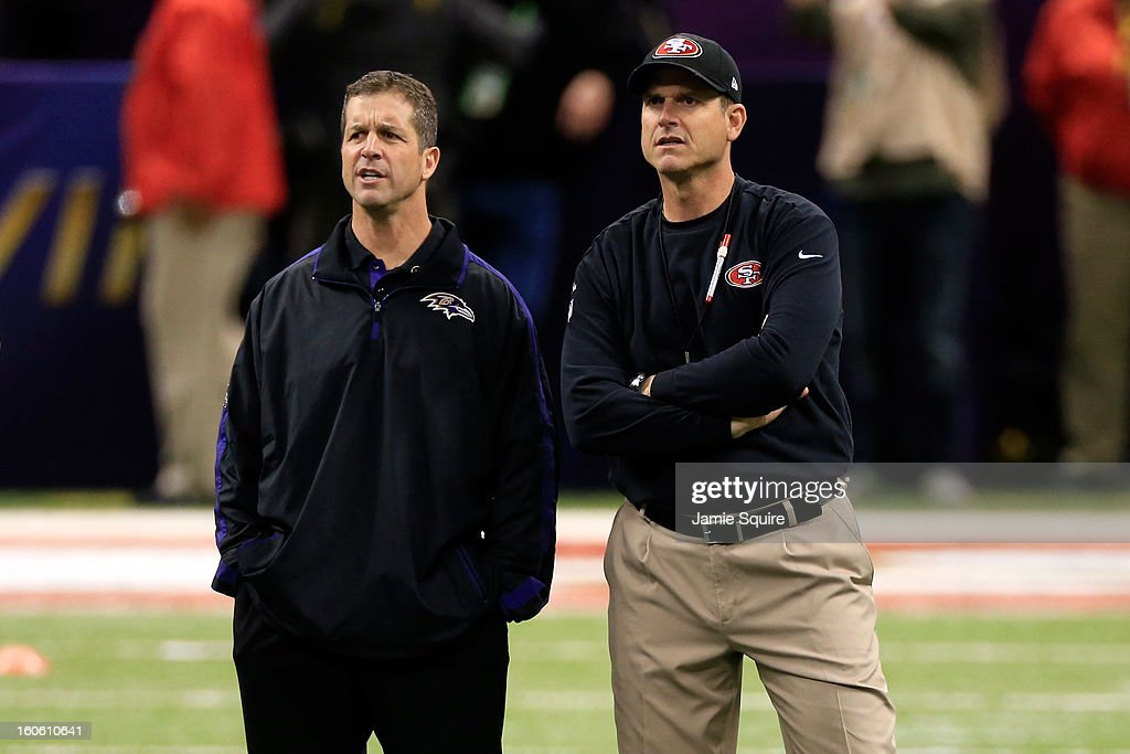 Head coach John Harbaugh of the Baltimore Ravens (L) and head coach Jim Harbaugh of the San Francisco 49ers speak during warm ups prior to Super Bowl XLVII at the Mercedes-Benz Superdome on February 3, 2013 in New Orleans, Louisiana.