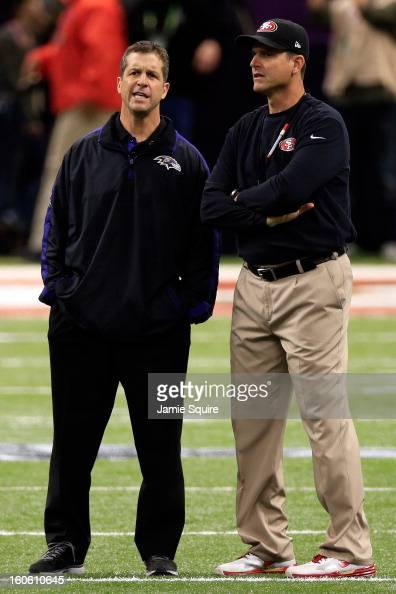 Head coach John Harbaugh of the Baltimore Ravens and head coach Jim Harbaugh of the San Francisco 49ers speak during warm ups prior to Super Bowl...