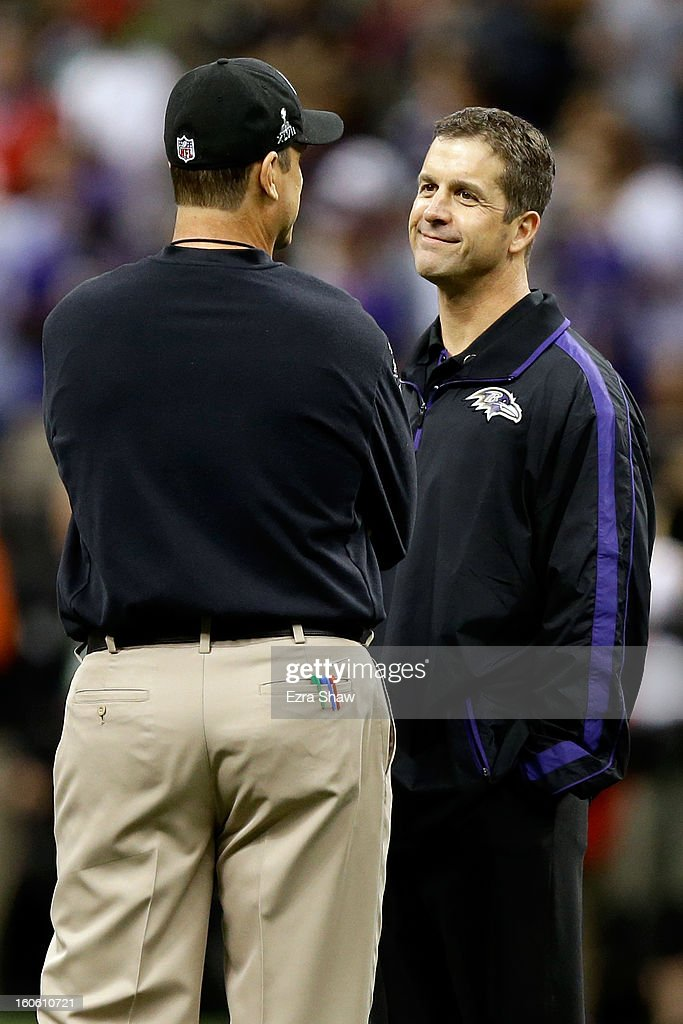 Head coach John Harbaugh of the Baltimore Ravens (R) and head coach Jim Harbaugh of the San Francisco 49ers speak during warm ups prior to Super Bowl XLVII at the Mercedes-Benz Superdome on February 3, 2013 in New Orleans, Louisiana.