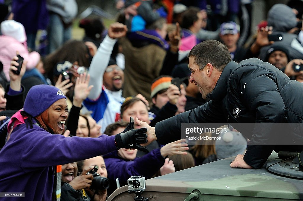 Head coach John Harbaugh (R) of the Baltimore Ravens celebrates with fans during their Super Bowl XLVII victory parade on February 5, 2013 in Baltimore, Maryland. The Baltimore Ravens captured their second Super Bowl title by defeating the San Francisco 49ers.