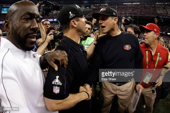 Head coach John Harbaugh of the Baltimore Ravens shakes hands with his brother head coach Jim Harbaugh of the San Francisco 49ers after winning Super...