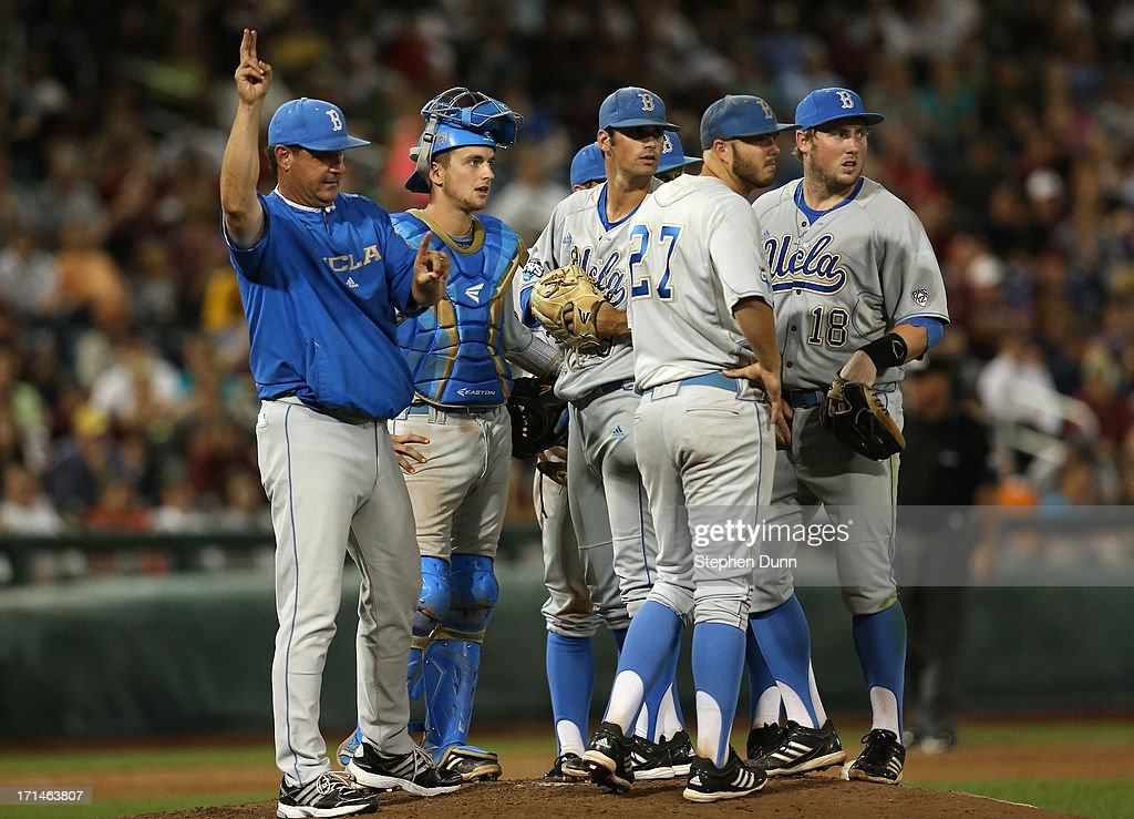 Head coach John Savage (L) of the UCLA Bruins calls for a relief pitcher for starter Adam Plutko #9 (third from left) against the Mississippi State Bulldogs during game one of the College World Series Finals on June 24, 2013 at TD Ameritrade Park in Omaha, Nebraska. UCLA won 3-1.