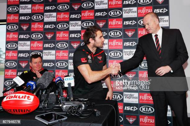 Head coach John Worsfold looks on as Jobe Watson shakes the hand of President Lindsay Tanner after announcing his retirement at the Essendon Football...