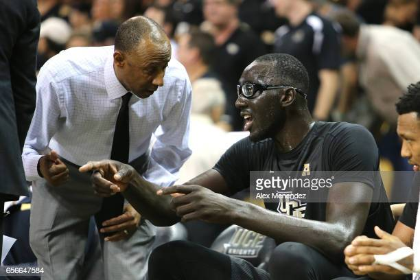 Head coach Johnny Dawkins of the UCF Knights speaks to Tacko Fall of the UCF Knights during the 2017 NIT Championship quarterfinal game between...
