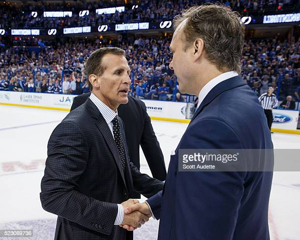 Head Coach Jon Cooper of the Tampa Bay Lightning shakes the hand of Assistant Coach Tony Granato of the Detroit Red Wings after the series win in...