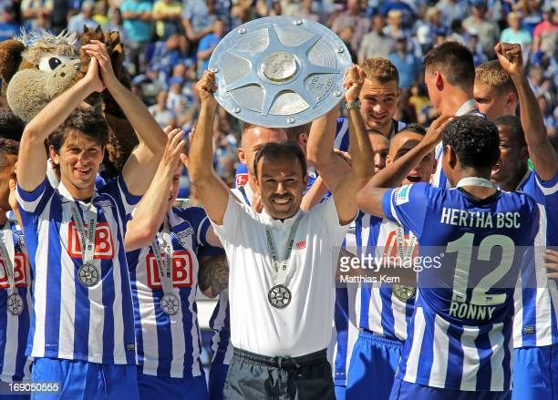 Head coach Jos Luhukay of Berlin and his team pose with the cup after winning the championship after the Second Bundesliga match between Hertha BSC...