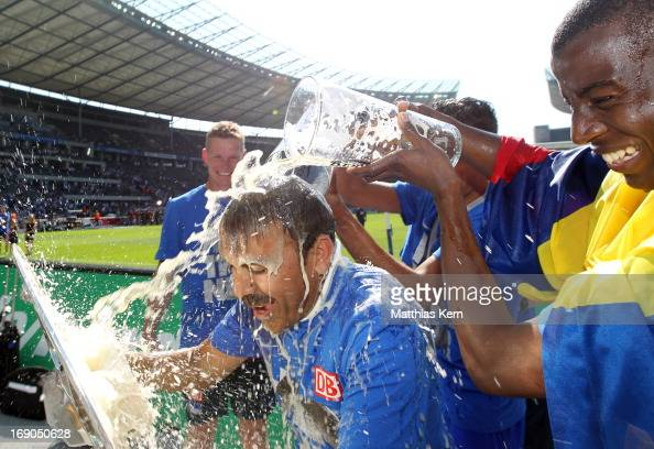 Head coach Jos Luhukay of Berlin gets a beer shower after winning the championship after the Second Bundesliga match between Hertha BSC Berlin and FC...