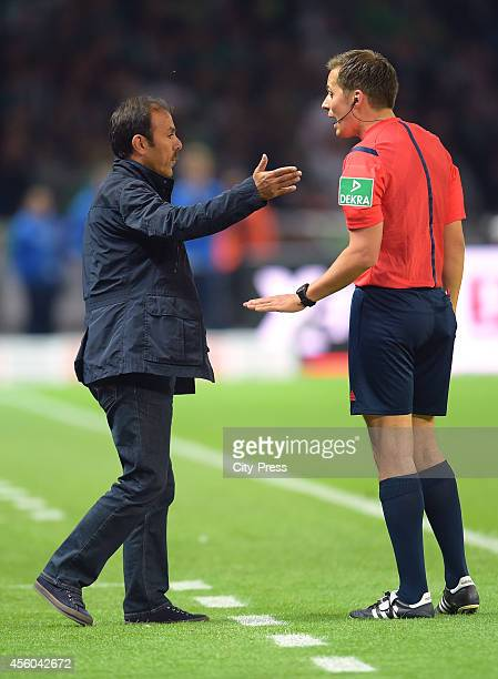 Head Coach Jos Luhukay of Hertha BSC speaks with referee Robert Hartmann during the Bundesliga match between Hertha BSC and VfL Wolfsburg on...