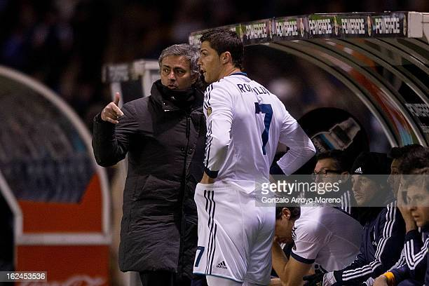 Head coach Jose Mourinho of Real Madrid CF gives instructions to Cristiano Ronaldo on the desk during the La Liga match between RC Deportivo La...