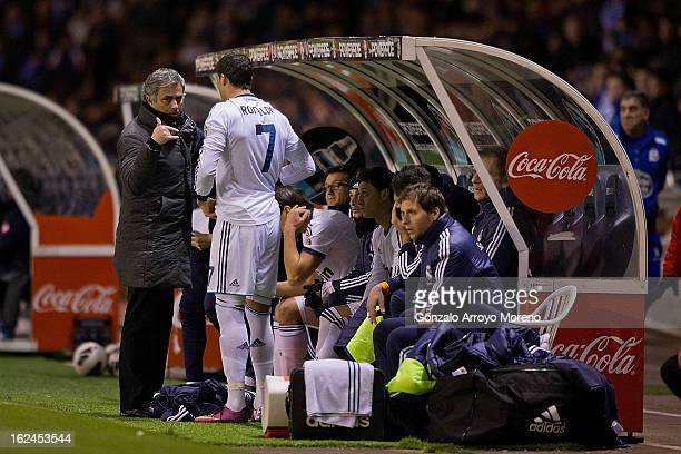 Head coach Jose Mourinho of Real Madrid CF gives instructions to Cristiano Ronaldo and Mezut Ozil on the desk during the La Liga match between RC...