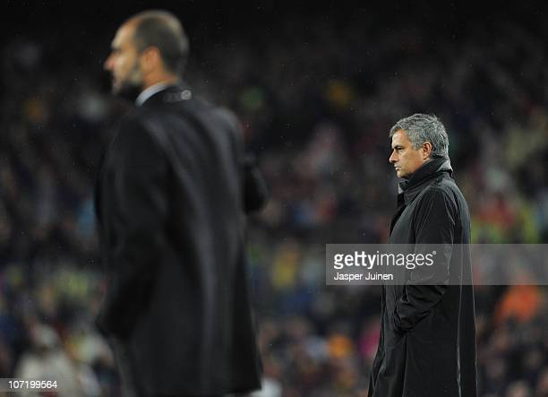Head coach Jose Mourinho of Real Madrid follows the game flanked by head coach Josep Guardiola of Barcelona during the la liga match between...