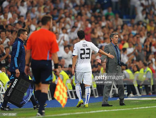 Head Coach Jose Mourinho of Real Madrid greets Mesut Ozil as he substitutes him at the end of the match during the UEFA Champions League group G...