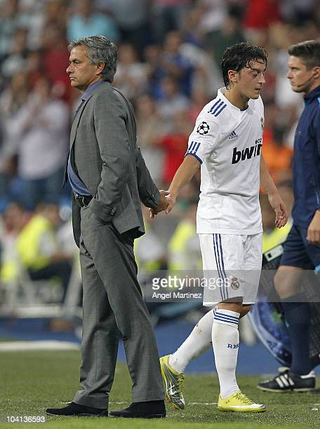 Head Coach Jose Mourinho of Real Madrid greets Mesut Ozil as he substitutes him during the UEFA Champions League group G match between Real Madrid...