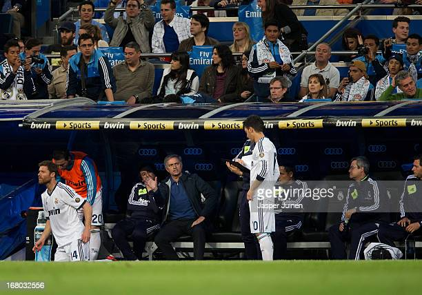 Head coach Jose Mourinho of Real Madrid intructs Mesut Ozil standing on the pitch getting ready to get on as a substitute during the la Liga match...