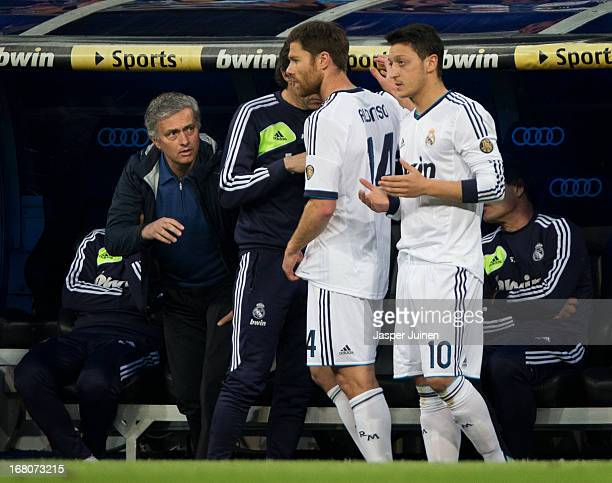 Head coach Jose Mourinho of Real Madrid intructs Xabi Alonso and Mesut Ozil while he brings them on as substitutes during the la Liga match between...