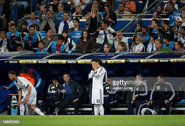 Head coach Jose Mourinho of Real Madrid looks at Mesut Ozil standing on the pitch getting ready to get on as a substitute during the la Liga match...