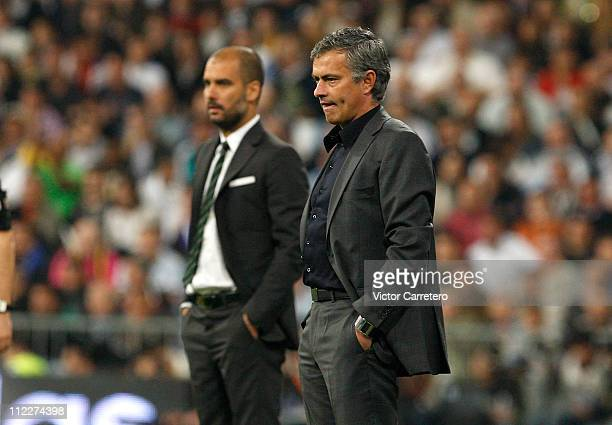 Head coach Jose Mourinho of Real Madrid looks on backdropped by head coach Josep Guardiola of Barcelona during the La Liga match between Real Madrid...