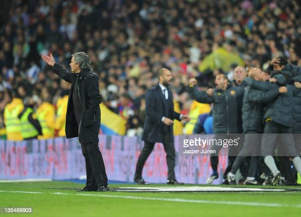 Head coach Jose Mourinho of Real Madrid reacts as head coach Josep Guardiola and players of FC Barcelona celebrate their sides third goal during the...