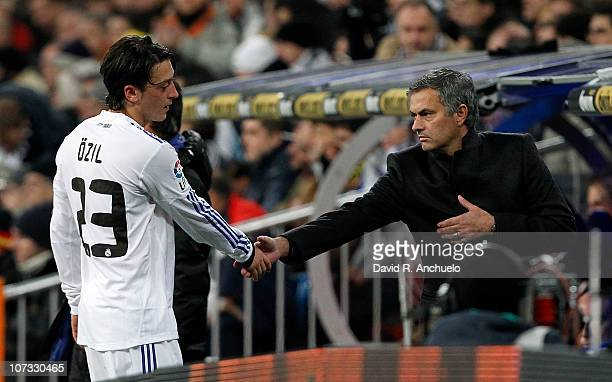 Head coach Jose Mourinho of Real Madrid shakes hands with Mezut Ozil as he is being subsituted during the La Liga match between Real Madrid and...