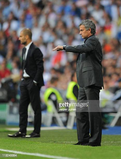 Head coach Jose Mourinho of Real Madrid stands backdropped by head coach Josep Guardiola of Barcelona during the UEFA Champions League Semi Final...