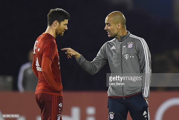 Head coach Josep Guardiola gives instructions to Xabi Alonso during a training session at day one of the Bayern Muenchen training camp at Aspire...