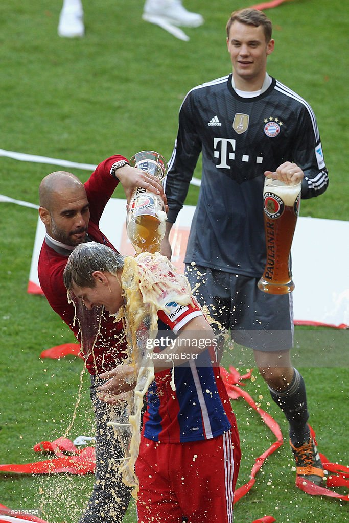 Head coach Josep Guardiola of Bayern Muenchen spoils beer over Toni Kroos while Manuel Neuer looks on to celebrate winning the German Championship after the Bundesliga match between FC Bayern Muenchen and VfB Stuttgart at Allianz Arena on May 10, 2014 in Munich, Germany.