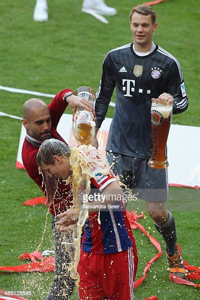 Head coach Josep Guardiola of Bayern Muenchen spoils beer over Toni Kroos while Manuel Neuer looks on to celebrate winning the German Championship...
