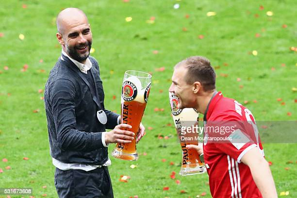 Head coach Josep Guardiola of Bayern Muenchen toast glasses with Holger Badstuber of Bayern Muenchen as they celebrate the Bundesliga champions after...