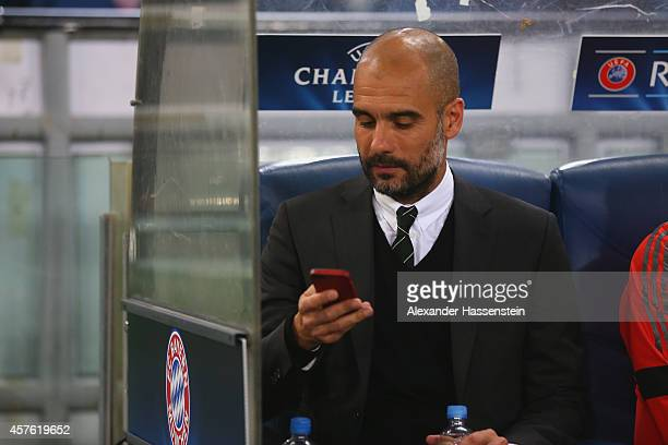 Head Coach Josep Guardiola of Bayern Muenchen uses his mobile phone before the UEFA Champions League group E match between AS Roma and FC Bayern...