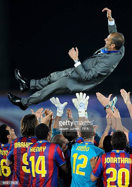 Head coach Josep Guardiola of FC Barcelona is thrown in the air by players after winning the Club World Cup Final match against Estudiantes at the...