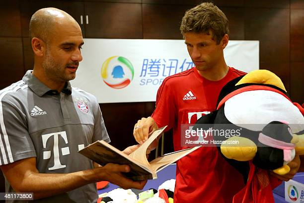 Head coach Josep Guardiola of FC Bayern Muenchen and his player Thomas Mueller receiving gifts after a table tennis match broadcasted live on TV at...