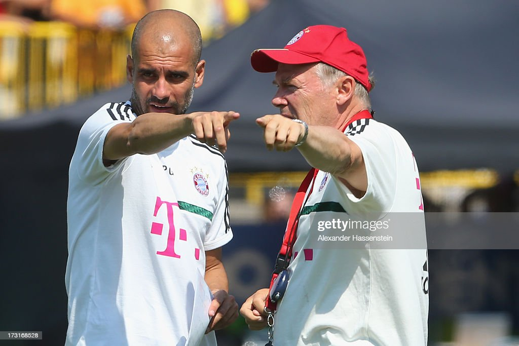 Head coach Josep Guardiola of FC Bayern Muenchen gesture with his assistent coach Hermann Gerland (R) during a training session at Campo Sportivo on July 9, 2013 in Arco, Italy.