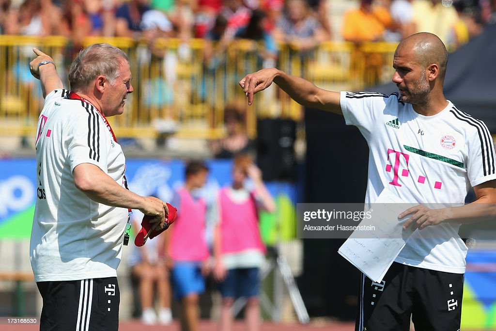 Head coach Josep Guardiola of FC Bayern Muenchen gesture with his assistent coach Hermann Gerland (L) during a training session at Campo Sportivo on July 9, 2013 in Arco, Italy.