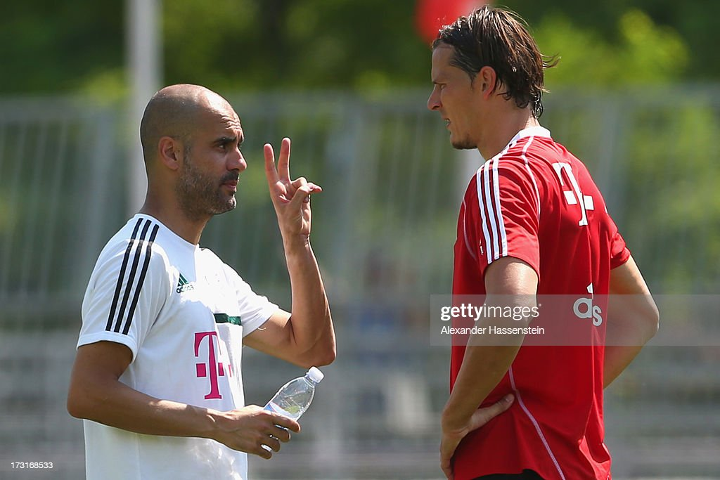 Head coach Josep Guardiola of FC Bayern Muenchen gesture with his polayer Daniel van Buyten during a training session at Campo Sportivo on July 9, 2013 in Arco, Italy.