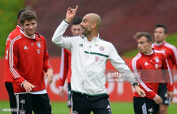 Head coach Josep Guardiola smiles with Thomas Mueller during a training session at day 2 of the Bayern Muenchen training camp at ASPIRE Academy for...