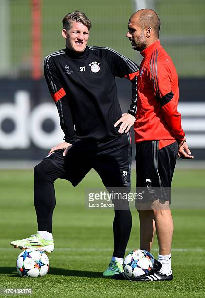 Head coach Josep Guardiola speaks with Bastian Schweinsteiger during a FC Bayern Muenchen training session prior to their UEFA Champions League...