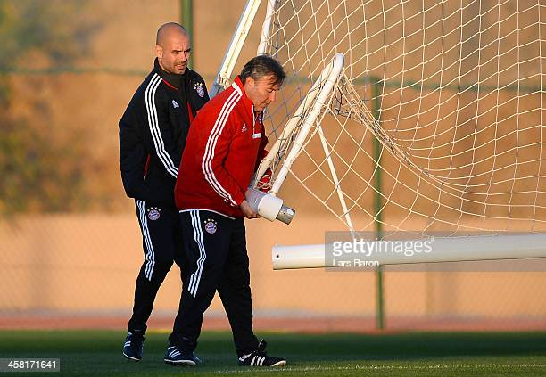 Head coach Josep Guardiola tries to fix a goalpost with his assistant coach during a Bayern Muenchen training session ahaed of the FIFA Club World...