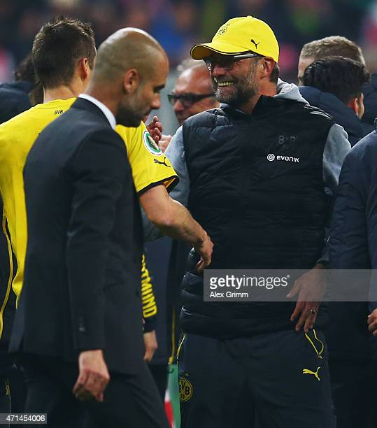 Head coach Juergen Klopp of Dortmund celebrates with the team as head coach Pep Guardiola of Muenchen reacts after the DFB Cup Semi Final match...