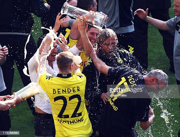 Head coach Juergen Klopp of Dortmund gets a beer shower from Sven Bender and Nuri Sahin after dortmund wins the German championship after the...