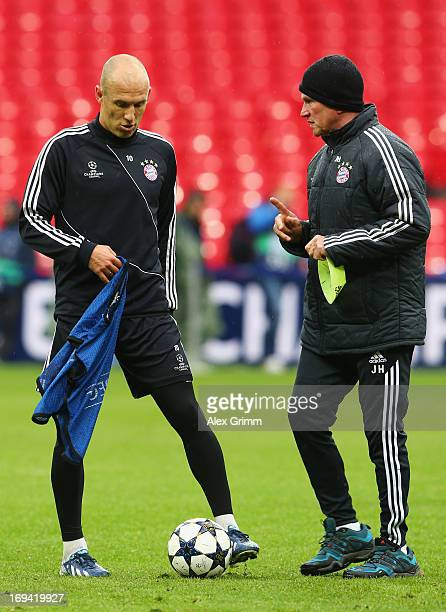 Head Coach Jupp Heynckes of Bayern Muenchen talks to player Arjen Robben during a FC Bayern Muenchen training session ahead of the UEFA Champions...