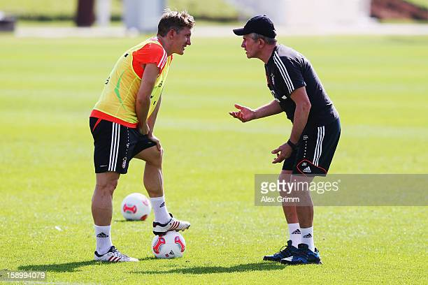 Head coach Jupp Heynckes talks to Bastian Schweinsteiger during a Bayern Muenchen training session at the ASPIRE Academy for Sports Excellence on...