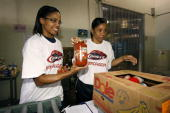 Head coach Karleen Thompson of the Houston Comets and Tamecka Dixon fill boxes with food for the victims of Hurricane Ike on September 19 2008 at the...