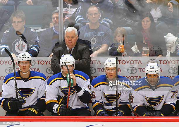 Head Coach Ken Hitchcock of the St Louis Blues looks on from the bench behind players Jori Lehtera Patrik Berglund Paul Statsny and Ryan Reaves...